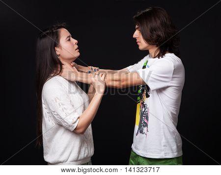 Domestic violence - man detaining woman black background