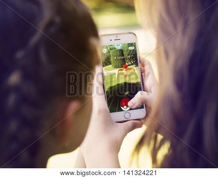Vienna, AUSTRIA - August 1, 2016: Little girls playing a Pokemon Go game outdoors. Pokemon Go is a location-based augmented reality mobile game.