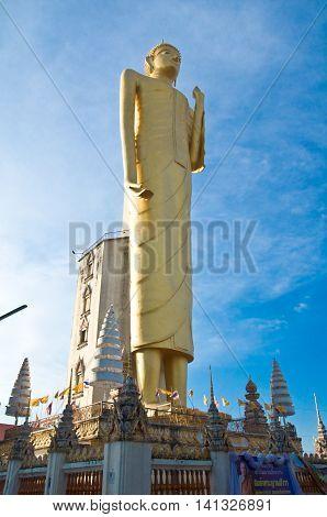 A 45 mtr tall golden Buddha set against a blue sky in Roi Et Thailand