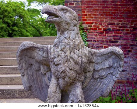 Stone egale statue with speed wings with wall and steps