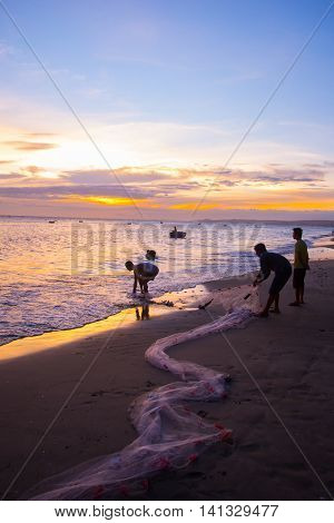 Fishermen At Sunset In Vietnam. Men Fish With Nets, Remove The Fish From The Sea.