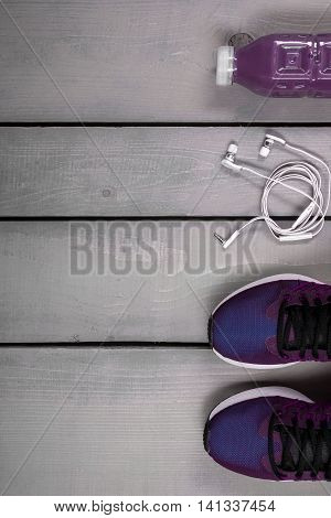 Overhead view woman's workout outfit. Female sports equipment. Purple running shoes water bottle and white headphones on grey wooden background. Top view. Copy space frame.