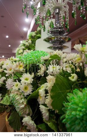 four tiered white wedding cake with green flower decoration