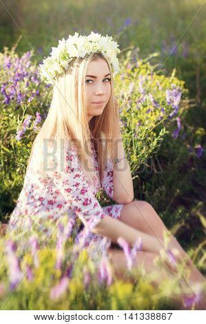 Blond girl with flower coronet sitting in the field with grass and purple flowers