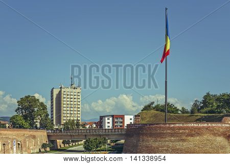 Alba Iulia Romania - July 24 2016: The Romanian flag raised in front of the Alba Carolina western entrance a Vauban bastion fortress built between 1715-1738.