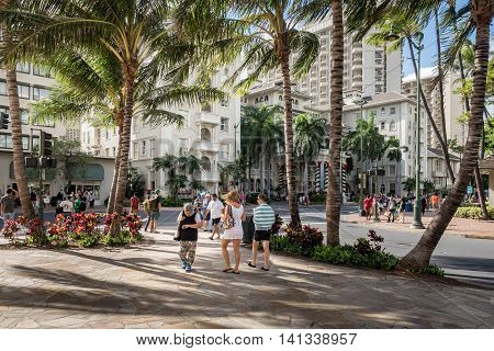 Waikiki, Honolulu, Hawaii, USA - Dec 21, 2015: At the corner of Kalakaua and Kaiulani Avenues. This area is very popular among tourists, day or night, since it is close to the famous Waikiki Beach, eateries, and shops.