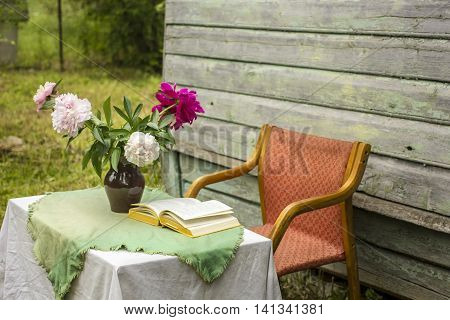 Vase of beautiful peony and a closed book on a table covered with a tablecloth nearby there is a the empty chair outdoor against a background old wooden house with peeling paint and tonsure of lawn with green grass a cloudy summer afternoon