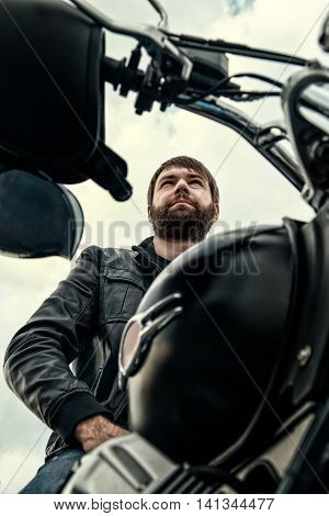 Biker Men With A Beard Sitting On His Motorcycle