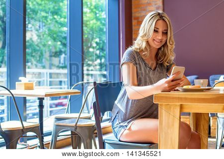Young Smiling Girl Read Something On Her Phone