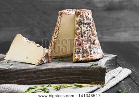 Goat cheese in shredded oak bark with white mold greens next to piece of sliced goat cheese black wooden background