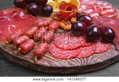 Meat-cutting sausage jerked cheese prosciutto smoked sturgeon nuts almonds pecans purple grapes on the round board dark black wooden background