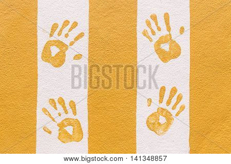 Hand print on orange and white wall