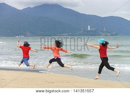 Women Jumping At China Beach In Danang In Vietnam