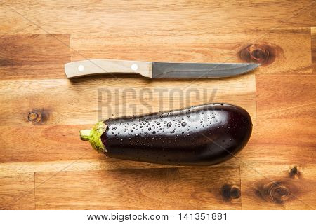 dewy fresh eggplant with knife on wooden table