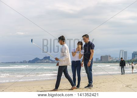 Young People Use Selfie Stick On China Beach In Danang