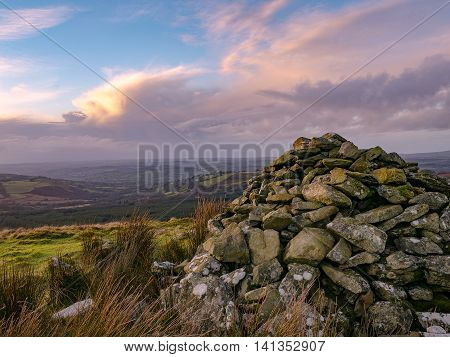 Sunset at Cairn on Esgair Fraith above Sarn Helen Roman road looking down the Ffryd Cynon valley towards the Teifi valley Wales UK.