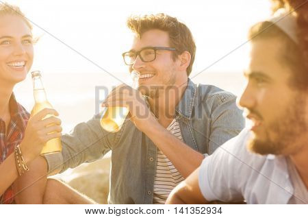 Young man and woman drinking beer while sitting on beach at sunset. Group of guys and girls out on a picnic drinking non alcoholic drink. Smiling friends celebrating with beers summer vacation.