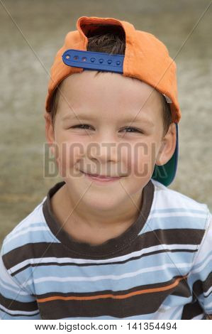 Beautiful boy with cap smiling with mischievous face