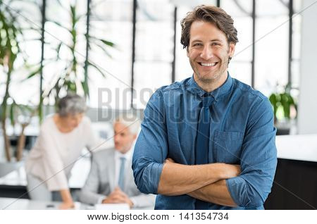 Portrait of cheerful businessman laughing and looking at camera. Happy business man standing with arms crossed at office while colleagues discussing in background.
