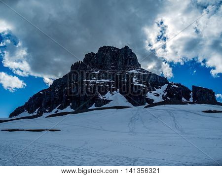 Mountain looming over a snow field at logan pass in Glacier National Park in Montana