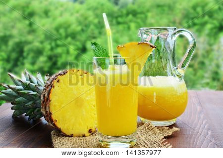 Refreshing pineapple mocktail drink in glass and pitcher with a piece of pineapple fruit on wooden table