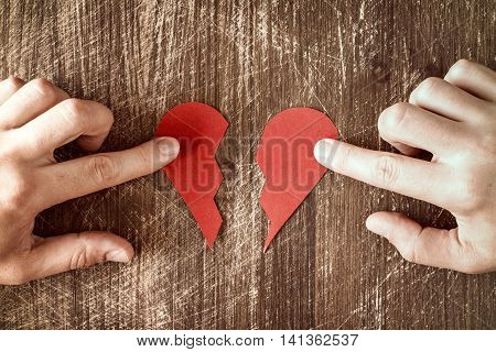 Hands holding two halves of broken heart going to be joined in one