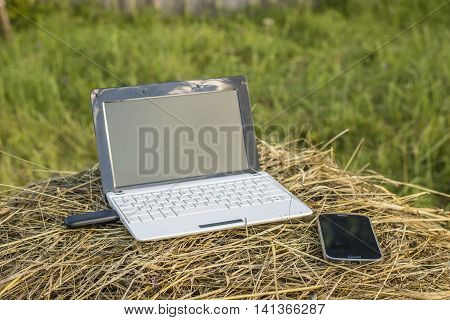 laptop with modem lies on a haystack near the phone evening at sundown