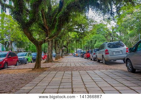 PORTO ALEGRE, BRAZIL - MAY 06, 2016: nice street with trees in the sidewalk and cars parked next to it.