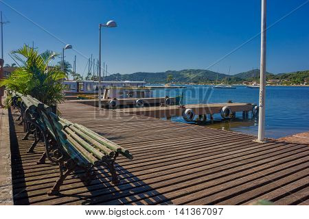 FLORIANOPOLIS, BRAZIL - MAY 08, 2016: some benches on the top of the dock close to some boats parked and a nice view of some houses at the end of the lake.