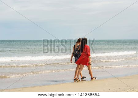 Danang Vietnam - February 20 2016: Young girls passing by at the China Beach in Danang in Vietnam. No face