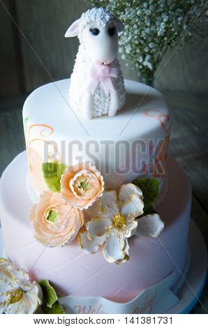 Baby shower cake with cute lamb topper and flowers
