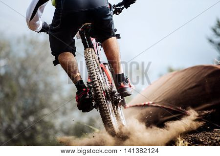 closeup of rear wheel of bike extreme racer on track downhill dust from wheels