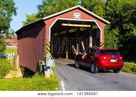 Lancaster PA - August 4 2016: The Landis Mill Covered Bridge spans the Little Conestoga Creek in Lancaster County. Built in 1873 it is now surrounded by extensive development and is the shortest covered bridge in the county.