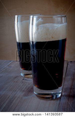 Glasses with kvass - flavored drink, reminiscent in taste non-alcoholic beer. On a wooden background.