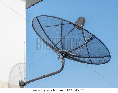 Black Satellite Dish Mounted On A Wall Outside The House. A Drop Of Water After Rain