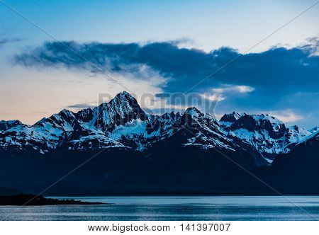 Tracy Arm Fjord AK USA - May 27 2016: Panorama of one of the many mountain peaks islands and forest areas as seen while cruising the Tracy Arm Fjord in Alaska. Darkening skies low clouds calm waters enhance reflections of the Tongass National Forest.