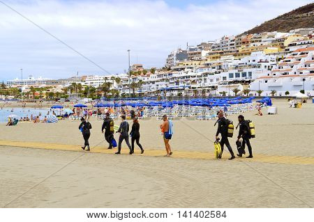 Los Cristianos beach Tenerife Canary Islands Spain Europe - June 13 2016: Scuba divers on the beach walking to the sea
