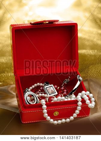 Red box with jewelry on gold background