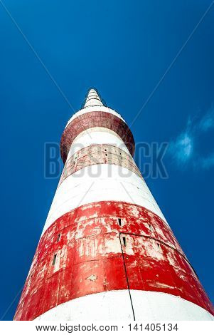 vertical image of a factory chimney red and white- v1