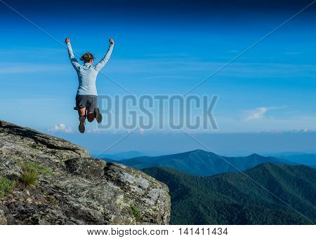 Leaping for Joy from a Rocky Overlook in summer
