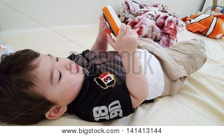 Adorable Asian baby boy laying on the floor holding a mobile phone toy