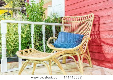Outdoor patio seating area in house with nice rattan table and chair. Cozy house