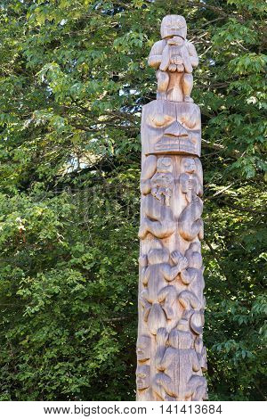 Vancouver Canada - July 24 2016: One of nine totem poles at Hallelujah point in Stanley Park. Plain wooden with images of man holding eagle eagle holding baby frog masks. Green trees as background.