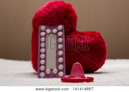 Medicine contraception love and birth control. Oral contraceptive pills condom on red heart shaped little pillow