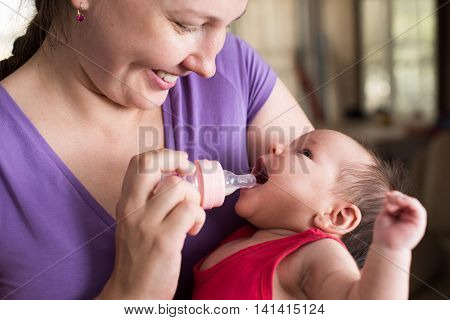 Young mother is feeding her newborn baby with bottle.