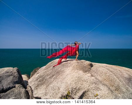 Woman on the rock in red flying dress
