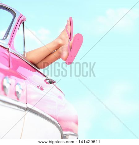 Summer fun vintage car. Legs showing from pink vintage retro car. Freedom travel and vacation road trip concept lifestyle image with woman and copy space on blue sky.