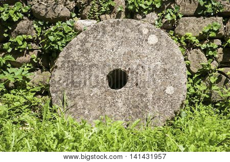 Old millstone closeup on stone wall background