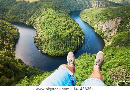Feet of the young man (traveler) in sneakers on the background of amazing landscape with Vltava river in Czech Republic.