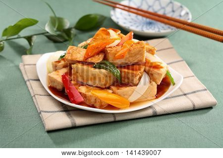 Sue fried tofu hot water with chili and onion on white plate on tablecloth